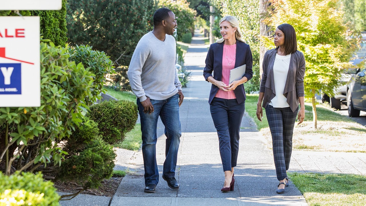 Photo of a realtor holding a tablet and two other people walking on a sidewalk